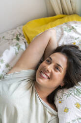 Smiling woman relaxing in bedroom - AFVF06864