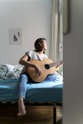 Woman playing guitar in bedroom - AFVF06873