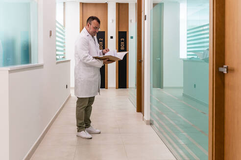 Dentist reading file while standing in corridor in hospital - DLTSF00925