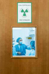 Doctor talking to nurses in dentist's clinic behind door - DLTSF00967