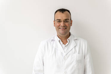 Smiling male doctor against wall in dentist's clinic - DLTSF00973