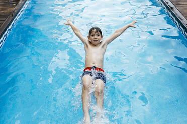 Boy doing backstroke jump in pool - JRFF04687