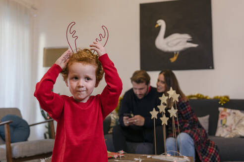 Cute boy wearing antlers looking away while parents sitting on sofa in living room during Christmas - EIF00165