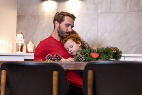 Father and son with Christmas wreath on table sleeping in kitchen at home - EIF00189