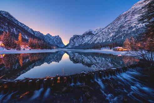 Dusk lights on the snowy peaks mirrored in Lake Dobbiaco, Val Pusteria, Dolomites, Bolzano province, South Tyrol, Italy, Europe - RHPLF17056