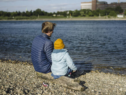 Father and daughter looking at Rhine river while sitting on log during sunny day - GUSF04331
