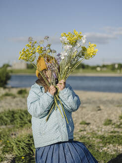 Girl holding flowers while standing on land against sky during sunny day - GUSF04340