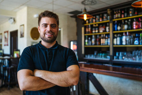 Bright young man in casual wear with crossed arms standing in own bar looking at camera - ADSF07549