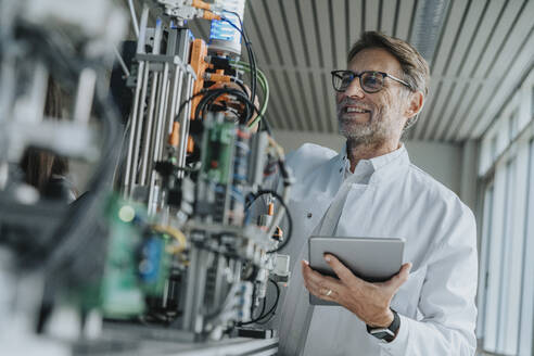 Smiling male scientist holding digital tablet examining machinery in laboratory - MFF05920