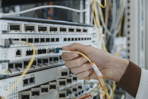 Close-up of woman plugging fiber optic cable in equipment at data center - MFF05956