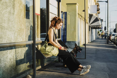 Woman using mobile phone while sitting with dog outdoors - MEUF01717