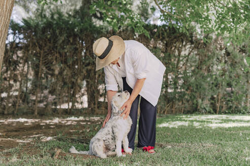 Senior woman wearing hat with dog standing on grassy land in yard - ERRF04118