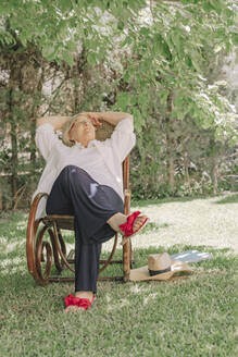 Thoughtful senior woman with hands behind head relaxing on chair in yard - ERRF04121