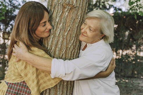 Mother and daughter looking at each other while embracing tree trunk in yard - ERRF04151