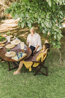 Cheerful mother and daughter enjoying picnic while sitting in yard - ERRF04160
