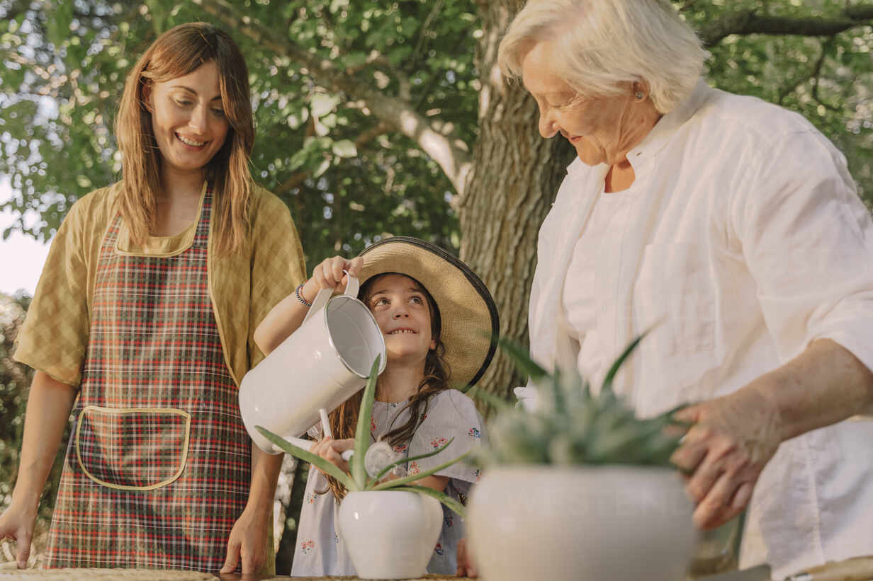 Smiling mother and grandmother looking at girl watering potted plant in yard - ERRF04172 - Eloisa Ramos/Westend61