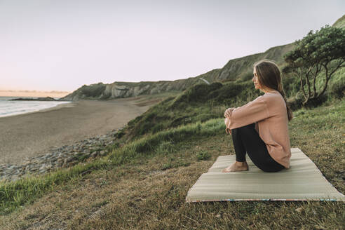 Thoughtful young woman sitting on exercise mat at beach against clear sky during sunset - MTBF00566