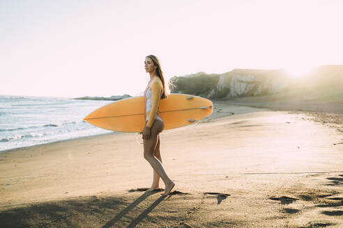 Young woman wearing wetsuit carrying surfboard at beach during sunset - MTBF00572