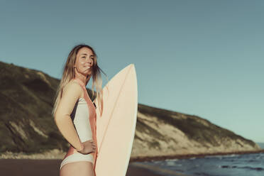 Smiling young woman with surfboard standing at beach against clear sky - MTBF00578