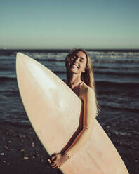 Cheerful woman with eyes closed carrying surfboard against sea during sunset - MTBF00581