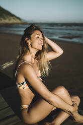 Smiling young woman wearing bikini with hand in hair sitting at beach during sunset - MTBF00584
