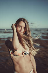 Smiling young woman in bikini standing against sea and clear sky during sunset - MTBF00593