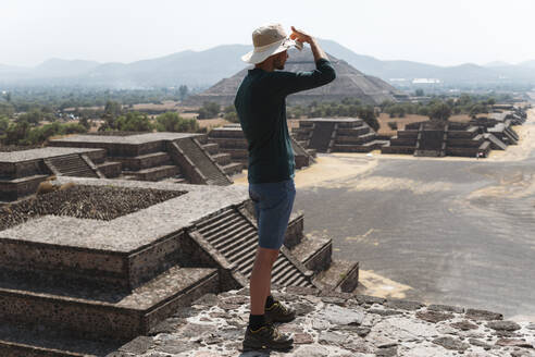 Mature man wearing hat standing on pyramid against sky in Teotihuacan, Mexico - JMPF00271