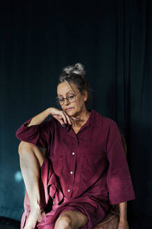 Thoughtful senior woman wearing eyeglasses sitting on chair against curtain at home - ERRF04194