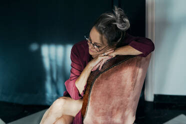 Sad senior woman contemplating while sitting on chair at home - ERRF04197