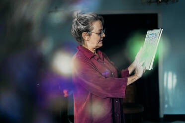 Senior woman holding drawing book while standing at home - ERRF04203
