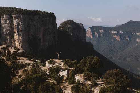 Mid distance of man with arms raised standing on mountain at Vilanova de Sau,  Catalonia, Spain - MOSF00123