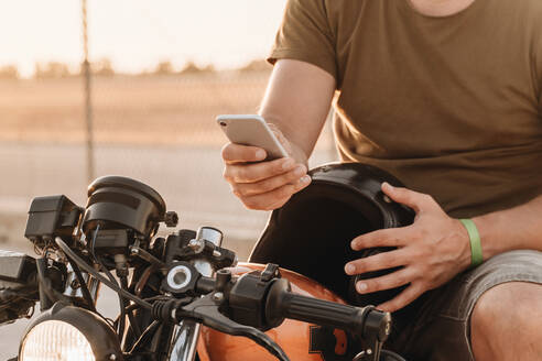 Man sitting on motorcycle and surfing mobile - ADSF08521