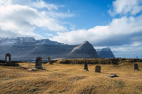 Ancient cemetery with old tombstones in field against backdrop of high mountains surrounding clouds on Faroe Islands - ADSF08719