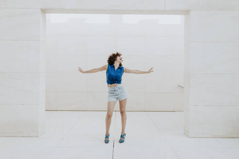 Carefree mid adult woman with arms outstretched standing against tiled wall - GMLF00376