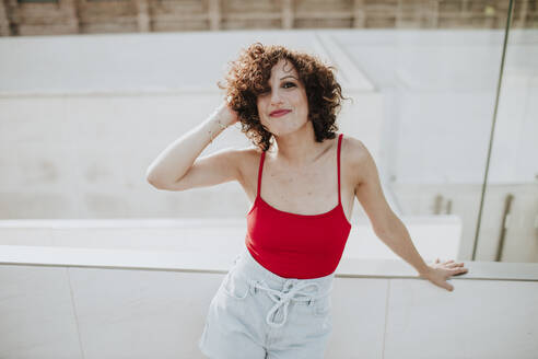 Smiling beautiful woman with curly hair standing by retaining wall in city - GMLF00382