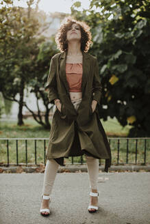 Mid adult woman with curly hair standing on footpath against plants in park - GMLF00391