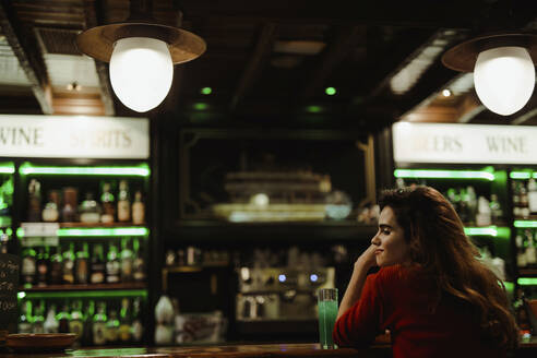 Mid adult woman with drink on bar counter sitting in illuminated restaurant - LJF01727