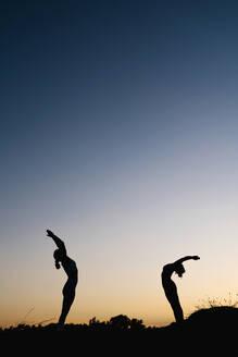 Women bending over backwards while practicing yoga outdoors - EGAF00630