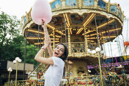 Cheerful beautiful woman holding cotton candy screaming while standing in amusement park - OYF00184