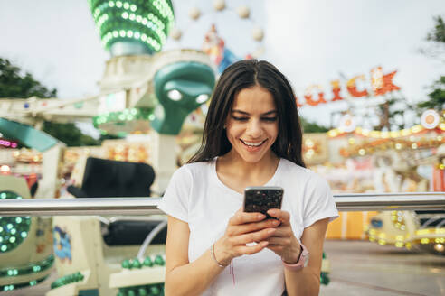 Smiling young woman using smart phone while standing in amusement park - OYF00193