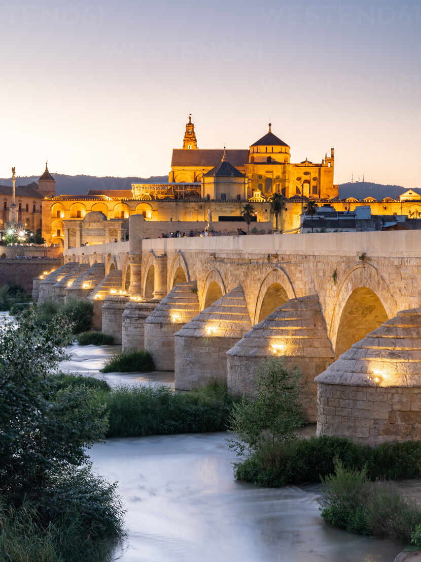 The Roman Bridge (Puente Romano) and The Great Mosque of Cordoba lit up  during evening sunset,