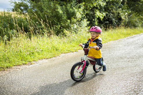 Toddler girl with pink cycling helmet on balance bicycle - BRF01485