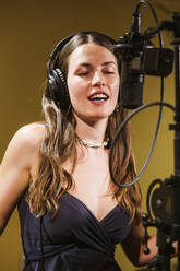 Singer with headphones at microphone in recording studio - LJF01739