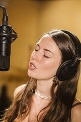 Singer with headphones at microphone in recording studio - LJF01742