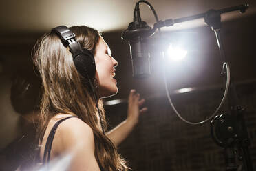 Singer with headphones at microphone in recording studio - LJF01745