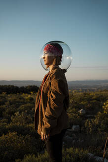 Woman with a fish bowl on her head in the countryside - RCPF00280