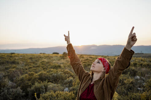 Woman with raised arms in the countryside looking up - RCPF00283