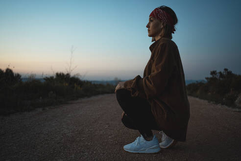 Woman crouching on a dirt road in the countryside at dusk - RCPF00286