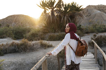 Smiling young tourist woman wearing Hijab on a wooden bridge - MPPF00985