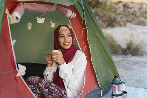 Smiling young tourist woman wearing Hijab in a tent holding a mug - MPPF00988